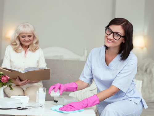 caregiver giving blanket to a senior woman