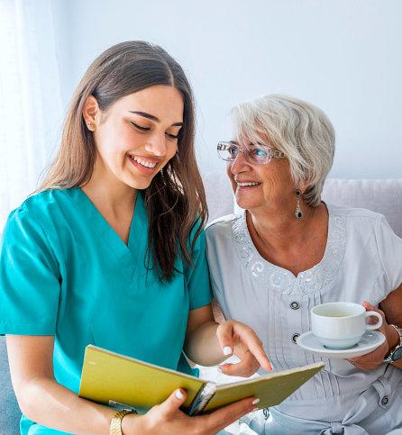 caregiver reading a book for a senior woman