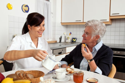 female caregiver preparing meal to senior woman